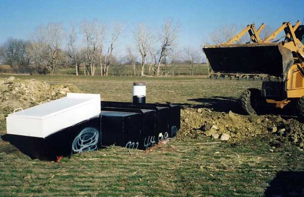 Below ground steel tornado shelter being buried