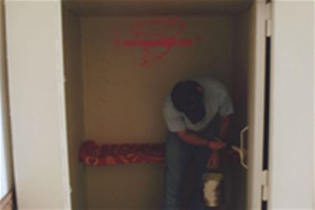 Installer painting interior of saferoom